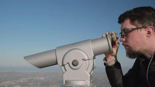 Man Focuses Binoculars on Observation Deck