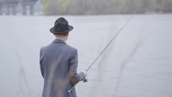 Thumbnail for Young Fisherman in a Jacket and a Cap with a Brim in the Early Morning Fishing in River