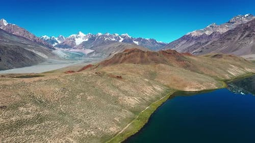 Aerial Shot Revealing Mountains , Glacier and River in the Backdrop of Chandratal Lake, Spiti