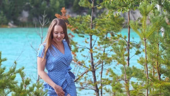 Smiling Pretty Woman in Blue Dress Walking on a Background of Blue Lake and Spruce Trees