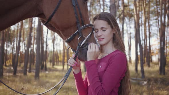 Thumbnail for Close-up of a Young Caucasian Girl in Pink Clothes Caressing Horse in the Autumn Forest and Smiling