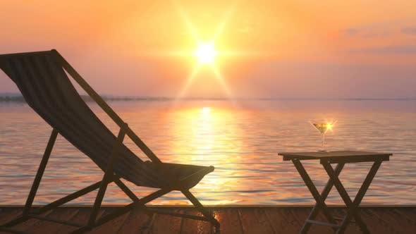 Thumbnail for Deck Chair and Table with Glass of Wine at Lake Coast Against Orange Sunset