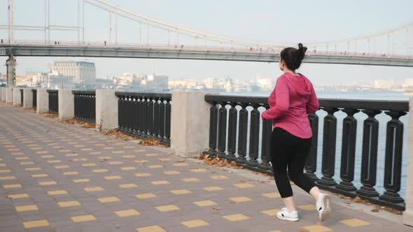 Thumbnail for Young cute female easy running alone city river in the morning. Training for marathon race