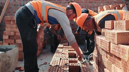 Builders Building a Brick Wall