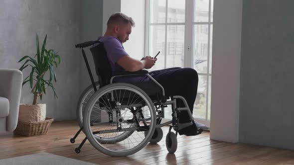 Thumbnail for Man using cell phone on wheelchair
