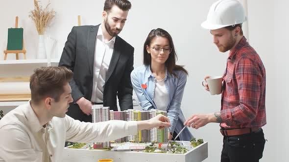 Kreatives Team von vier Architekturingenieuren arbeitet in einem Architekturstudio zusammen