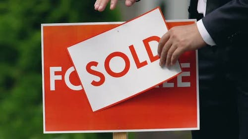 Male Agent Setting Sold Sign Outdoors, Real Estate Company, House Ownership