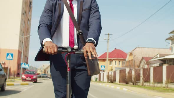 Midsection of Businessman Driving Electric Scooter on Road