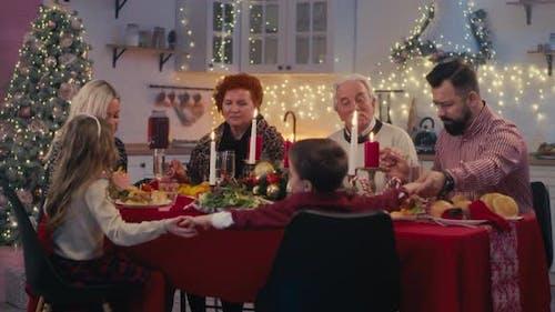 Religious Family Praying Before Christmas Dinner