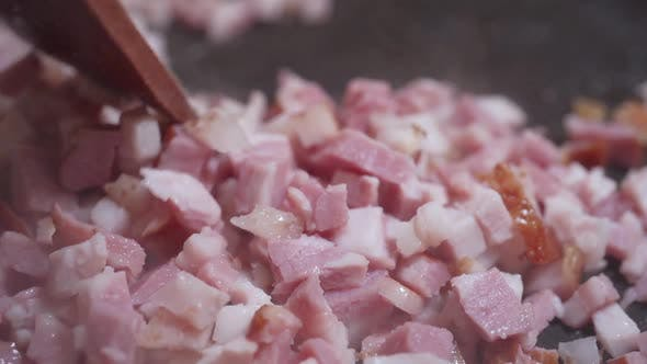 Thumbnail for A Cook with a Wooden Spatula Stirs the Chopped Bacon Are Fried in a Hot Frying Pan