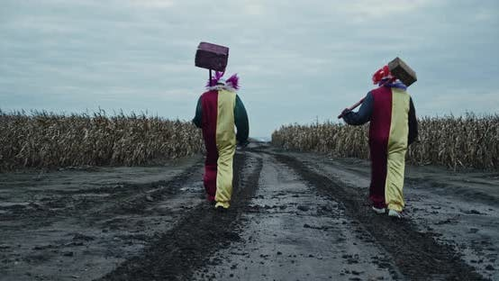 Two Scary Clowns Are Walking Along A Corn Path