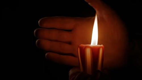 Bougie brûlante et main humaine
