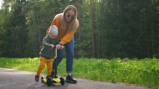 Thumbnail for Junge Mutter zeigt ihr Kleinkind Sohn, wie man einen Roller in einem Park fährt. Aktive Familienfreizeit
