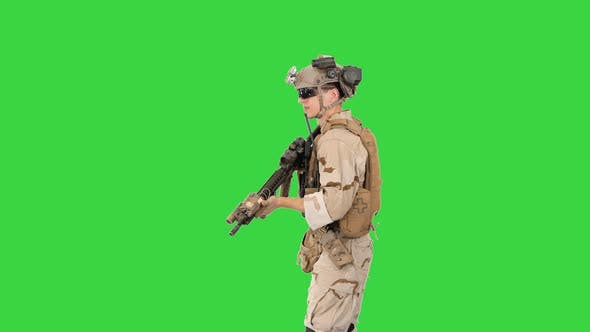 Soldier Aiming with an Assault Rifle on a Green Screen, Chroma Key.