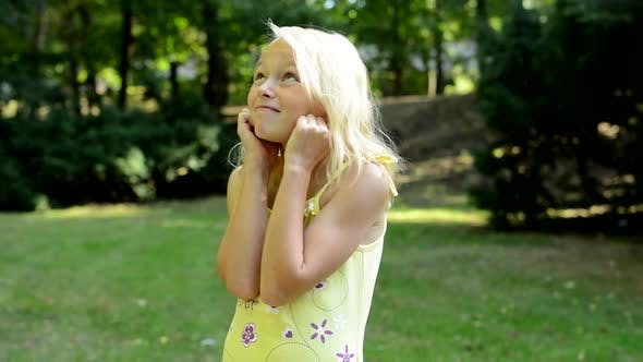 Thumbnail for Little Upset Girl Covers Her Ears with Fingers in the Park - Annoyed