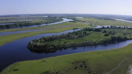 Scenic Aerial View of a River and Green Fields in a Countryside