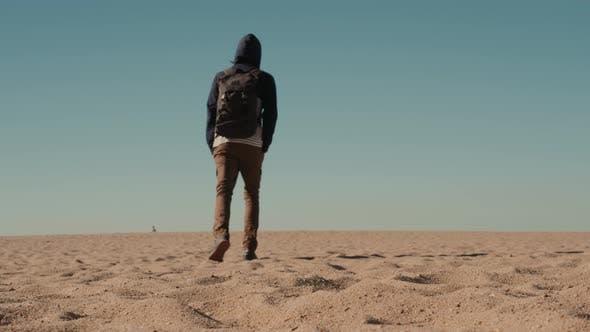 Man Walking Alone in the Sunny Desert Near Dubai Backpack Tourist Alone