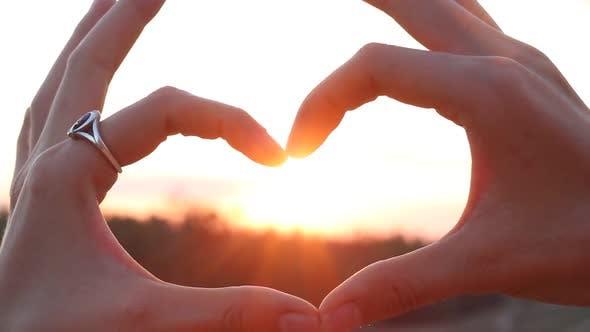 Thumbnail for Frau zeigt das Herz bei Sonnenuntergang