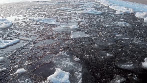 The Ice Is Near the Shore Close-up. Ice in Cold Water Floats Adrift