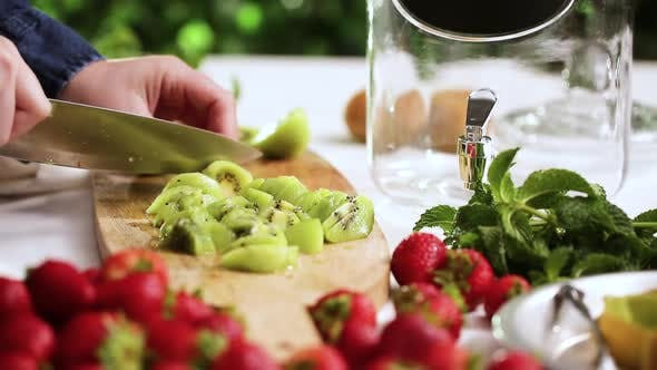 Step by step. Slicing fresh organic kiwi for infused water.