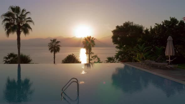 Thumbnail for Vacation Scene with Swimming Pool Overlooking Sea and Mountains at Sunset