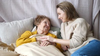Granddaughter Taking Care Of Her Grandmother In Bed. Elderly Care Concept
