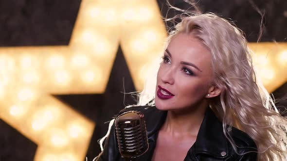 Thumbnail for Blonde Woman Singing with Retro Microphone, Shining Star in the Background, Slow Motion, Close Up