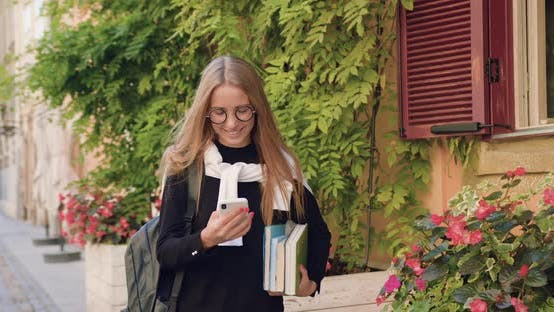 Thumbnail for Young Blond in Casual Clothes Walking Near Buildings with Green Plants and Using Her Smartphone
