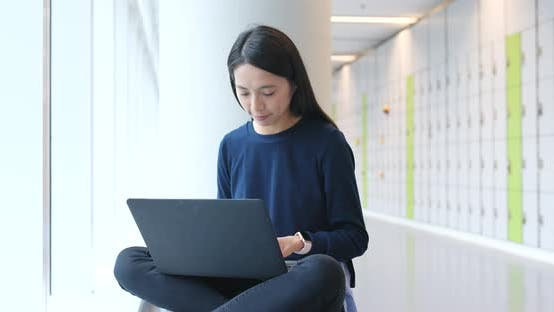Thumbnail for Woman working on notebook computer inside building
