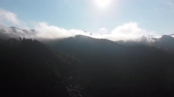 Thumbnail for Aerial View of Dawn Over the Mountains. Flying Through the Clouds. Sunrise