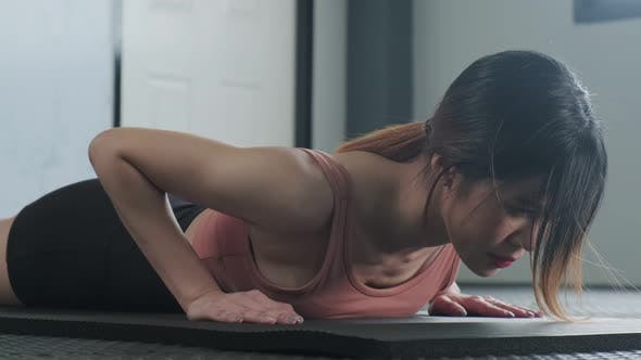 Asian young woman practicing the Bhujangasana Yoga pose or cobra pose of downward in fitness gym.