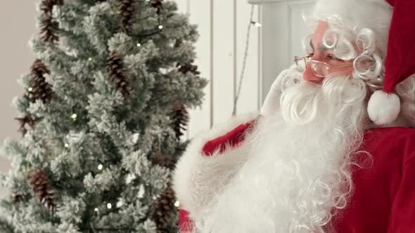 Thumbnail for Jolly Santa Claus Sitting By the Christmas Tree and Talking on the Phone