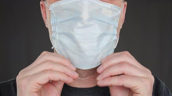 Nahaufnahme Erwachsener Mann Putting auf Gesichtsmaske Frontkamera. Männliches Gesicht trägt Schutzmaske.  Schutz