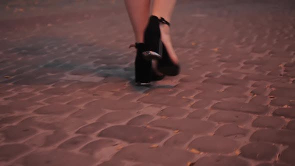 Beautiful Female Slim Legs in Sandals on Steady Stylish Black Heel Gracefully Walk Along the Cobbles