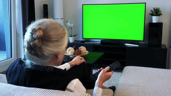Thumbnail for Old Caucasian Woman Watches Television in Living Room and Switches Program