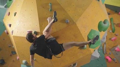Strong Man Practicing Climbing on Artificial Rock Wall