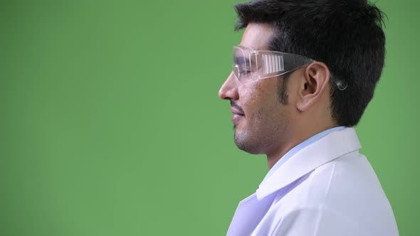 Thumbnail for Profile View of Young Handsome Persian Man Doctor Wearing Protective Glasses