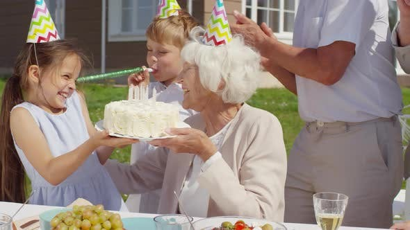 Thumbnail for Girl Bringing Birthday Cake to Grandmother at Family Party