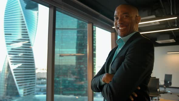 Thumbnail for African American Boss Standing Near Huge Modern Office Window and Smiles.