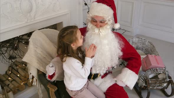 Thumbnail for Santa Claus Sitting in a Chair with a Little Girl Dreaming About Her Christmas Presents