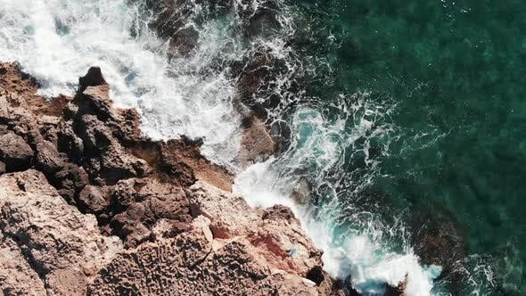 Rocky Seashore Hit by White Extreme Waves Splashing and Creating White Foam