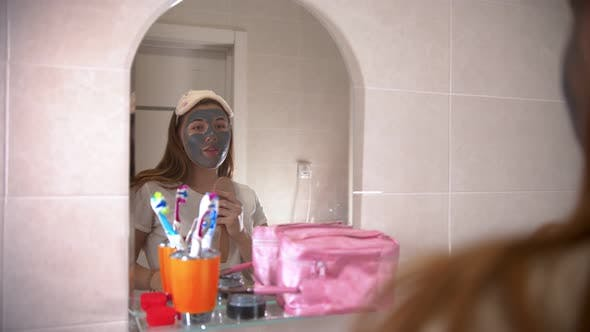 Thumbnail for A Young Woman with a Mask on Her Face Dancing and Singing in Front of the Mirror