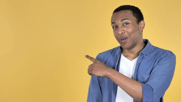 Cover Image for Young African Man Pointing with Finger on Side, Yellow Background