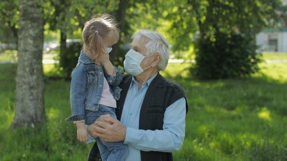 Großvater mit Enkelin nimmt Masken nach Coronavirus Quarantäne Ende