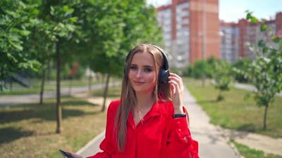 Lovely girl outdoors. Portrait of a young woman with headphones.