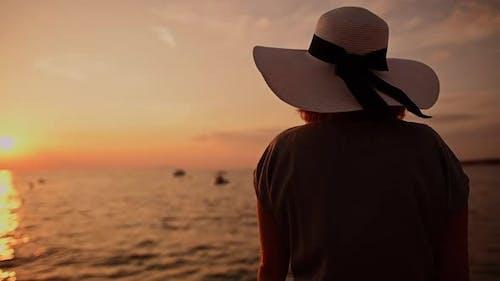 Woman Wearing Large Sun Hat Seating Next to Sea During Sunset