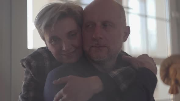 Thumbnail for Portrait of a Mature Couple Embracing While Sitting on the Floor at Home