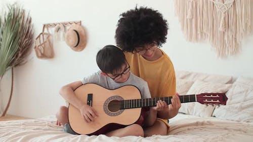 Woman Teacher Teaches Child to Play Acoustic Guitar