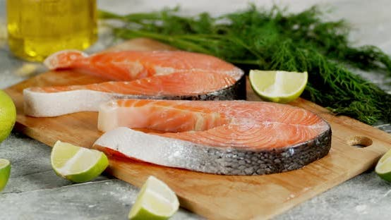 Raw Salmon Steaks with Pieces of Lime Rotate on the Table