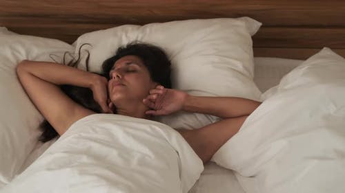 Young Woman is Sleeping in Her Bedroom at Sunny Morning Tossing and Turning